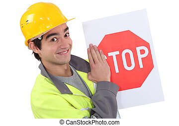 A young road worker holding a stop sign.