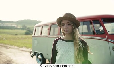 A young sad girl on a roadtrip through countryside, standing...