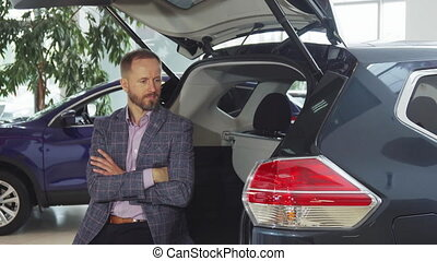 A young seller in a suit sits at the open trunk of the car