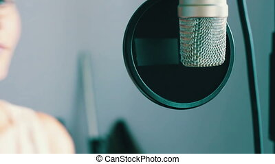 A young sexy girl sing in studio microphone