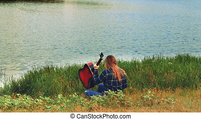 A young simpotichnaya girl tunes the guitar, she is sadly lonely when the sun goes over the horizon.