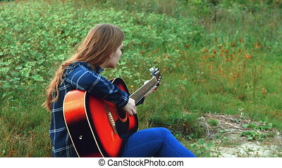 A young simpotichnaya girl tunes the guitar, she is sadly lonely when the sun goes over the horizon. 4k.