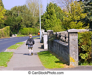A young six year old boy walking home by himself