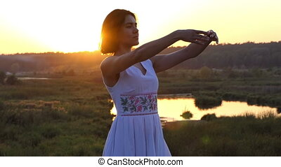 a Young Slim Woman Does Ballet Movements With Her Hands at Sunset in Slo-Mo