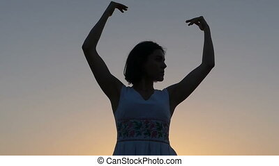 a Young Slim Woman Does Dancing Movements With Her Hands at Sunset in Slo-Mo