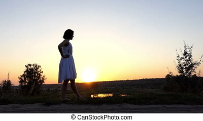 a Young Slim Woman Raises Her Straight Leg at Splendid Sunset in Slo-Mo