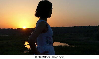 a Young Slim Woman Stands on a Lake Bank at a Splendid Sunset in Slo-Mo
