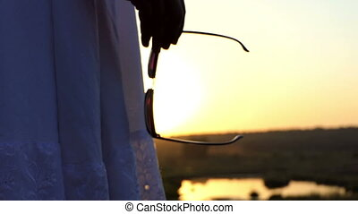 a Young Slim Woman Stands With Sunglasses in Her Hands at Sunset in Slo-Mo