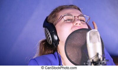 A young smiling woman in headphones singing song in the studio