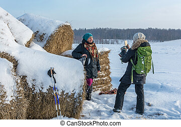 A young smiling woman is standing near a haystack. - A young...