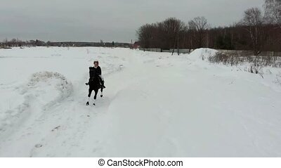 A young smiling woman riding a horse on a snowy field. Wide...