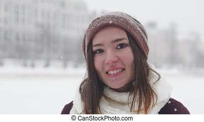 A young smiling woman standing in winter outside. Wearing white scarf