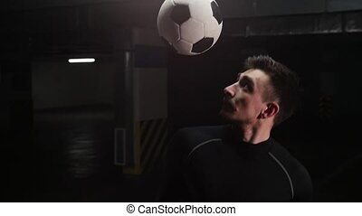 A young soccer man hitting the ball with his shoulder