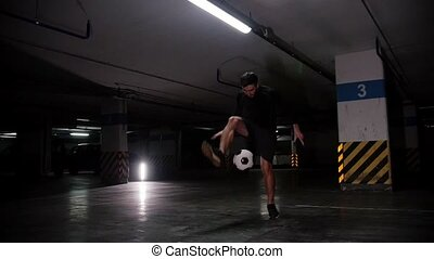 A young soccer man training his football skills with the ball in the underground parking