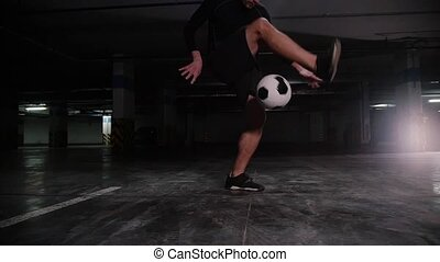 A young soccer man training his football skills with the...