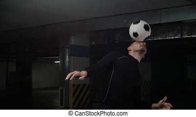 A young soccer man training tricks with the ball. Balancing...