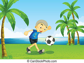 A young soccer player at the riverside with palm trees
