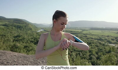 A young sports girl in sports wear who runs in the fresh air in the mountains at sunset listening to music with earphones from her smartphone. Healthy lifestyle