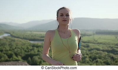 A young sports girl in sports wear who runs in the fresh air in the mountains at sunset listening to music with earphones from her smartphone. Healthy lifestyle. Close Up