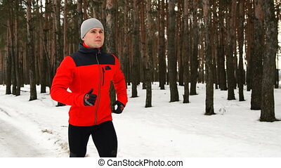 A young sports man goes in for sports in the forest on a run...