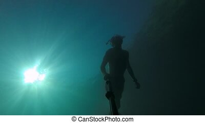 A young sports man in a mask and a snorkel swims with a selfie stick deep underwater underwater. Sun glare through the water