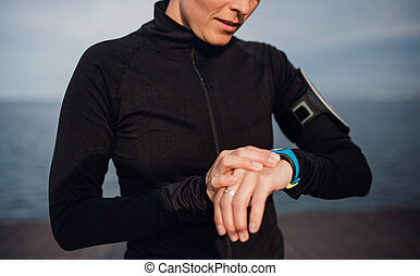 A young sportswoman standing outdoors on beach, using smartwatch.