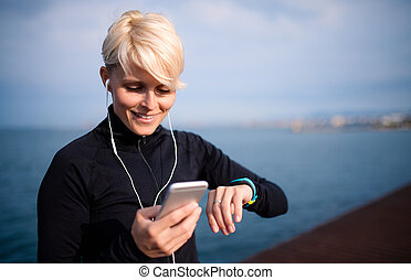 A young sportswoman with earphones standing outdoors on beach, using smartphone.