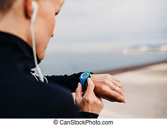 A young sportswoman with earphones standing outdoors on beach, using smartwatch.