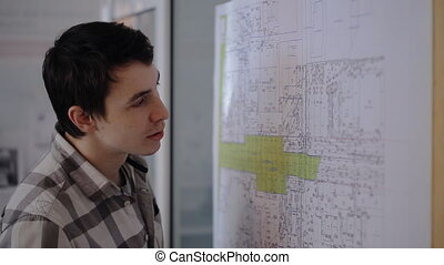 A young student engineer working on communications plan of city with pencil in hand.