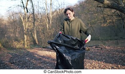 A young student preparing to collect garbage in the woods, opens a large black garbage bag. Nature aid, polluted ecosystem 4k