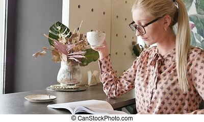A young student with glasses is studying English in a cafe. Cute blonde leafing through a magazine and drinking tea, sitting by the window at the tables in the cafe. Slow motion