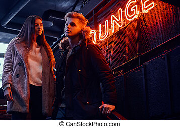 A young stylish couple wearing warm clothes standing on the staircase to the underground nightclub, a backlit signboard in the background