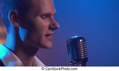 A young stylish guy vocalist singing and gestures with his hands on stage in a vintage microphone. Dark studio with smoke and neon lighting. Dynamic neon lighting effects. Performance vocal and musical band. Close up