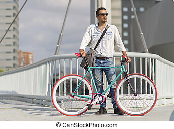 A young stylish man with sunglasses posing next to his bicycle.