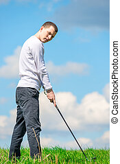 A young successful golfer prepares to hit the ball with a golf club on the field
