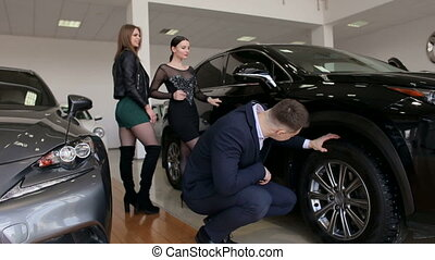 A young successful man with two girls chooses a new car in the showroom.