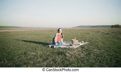 A young sweet girl arranged a picnic in the nature under soap bubbles. A little girl's dream in glasses on a picnic. Bubble.