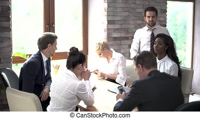 A Young Team of Business Partners are Preparing For An Important Meeting in a Sunny Meeting Room.