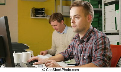 A young team of men working on a project in the office at the computer. Check the documents on taxes and fill out the electronic form. Teamwork to solve problems