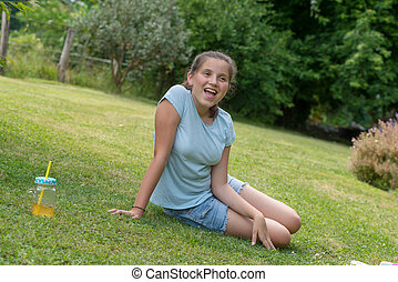 young teenager girl sitting in the grass
