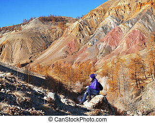 A young tourist is sitting on a rock and looking at the beautiful mountain topography. Multicolored paint of rock.