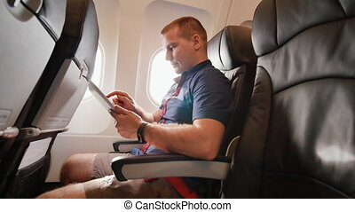 A young tourist on the plane works with the tablet before leaving.