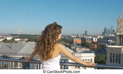 A young white woman looks at the panorama of the city.