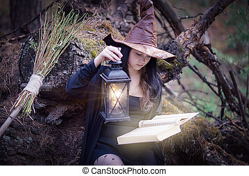 A young witch in the woods sits on a stump, reading a book, illuminating it with an antique lamp.