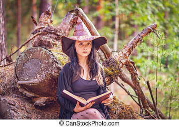 A young witch sits in the woods on a stump with a book.