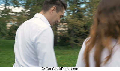 A young woman and a man in white suits are walking in the park. Hold hands, in the blur zone.
