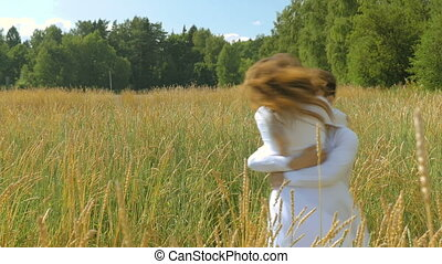 A young woman and a man in white suits flee to meet each other and embrace. On a sunny day, in a field with wheat.