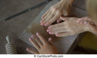 A young woman and her little son on a pottery master class.