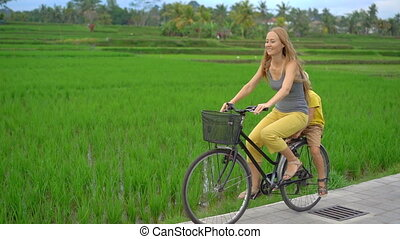 A young woman and her little son ride through the beautiful rice field on a bicycle. Travel to South-East Asia concept. Slow motion shot