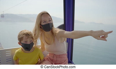 A young woman and her son wearing a black face masks ride in a cable car or a ropeway or aerial tram over the sea. Lockdown is over but people have to wear face masks everywhere. Economy reopening concept.